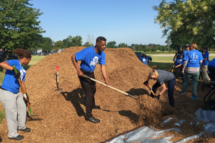 Flint City Councilman Eric Mays was among the volunteers helping to spread mulch at the new playground at Hasselbring Senior Center.