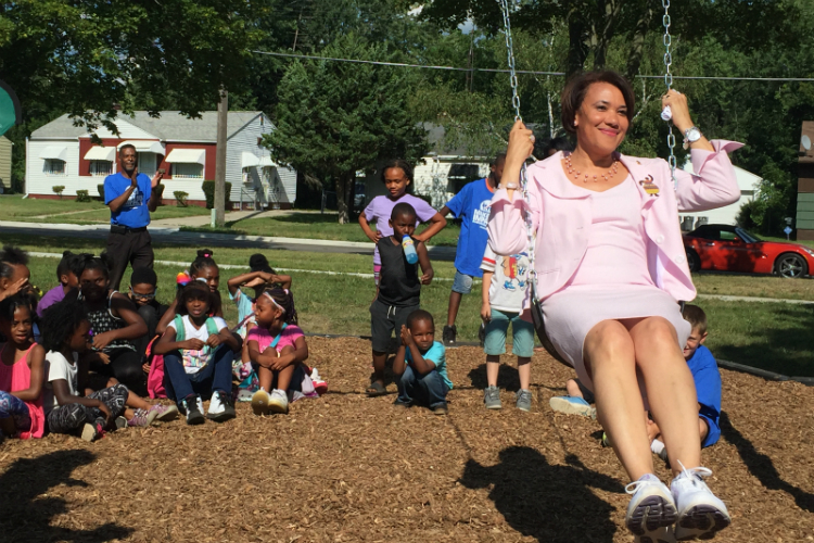 Flint Mayor Karen Weaver tries out the swings installed as part of the new playground at Hasselbring Senior Center.