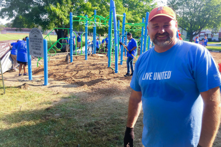 Jamie Gaskin, United Way of Genesee County CEO, helps oversee the work at the playground build Tuesday at Hasselbring Senior Center.
