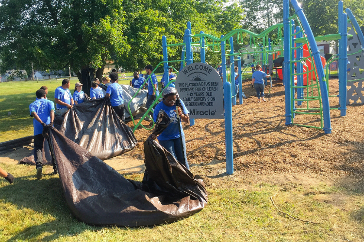 Volunteers use tarps to haul wood chips to mulch the area around the playground.