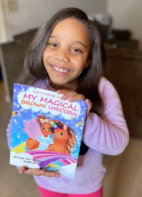 Kameryn Lowe holding up a copy of 'My Magical Brown Unicorn.'