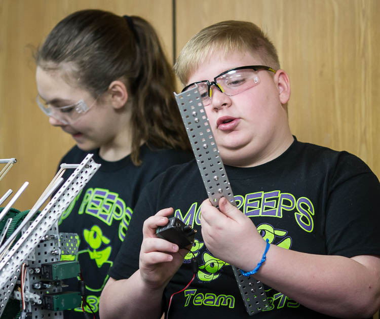 Max Johnson, 11, a student at Rankin Elementary works on a building a robot during a demonstration of the robots team skills at Woodland Elementary.