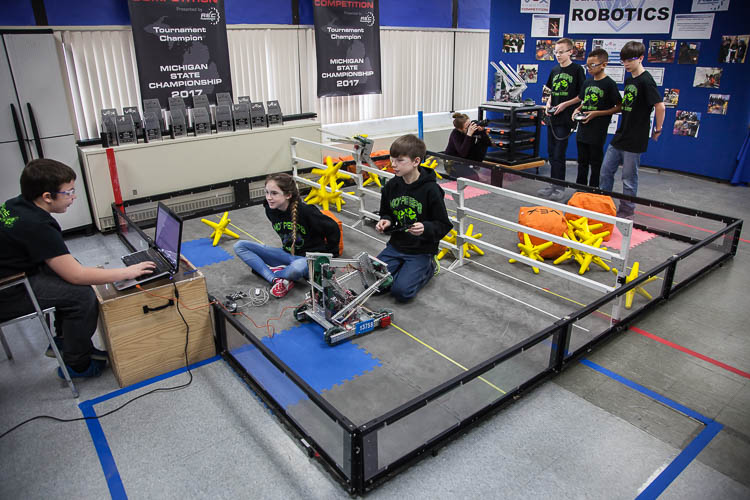 Parker Oosterhof, 12 (left); Lydia Minzey, 12; and Alex Wickham, 13, (right) work to program a robot for competition. In background are Caleb Rose, 13, (left); Micah Shamly, 12; and Jack Roy, 12, (right) who demonstrate driving the robot and picking