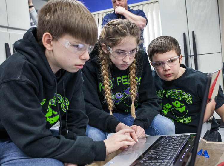 Alex Wickham, 13, (left); Lydia Minzey, 12; and Parker Oosterhof, 12, (right) work to program a robot for competition. The students are members of the Carman-Ainsworth Middle School team traveling to Louisville, Kentucky for the world robotics champi