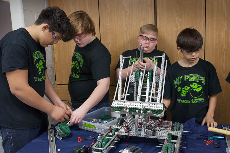 (From left) Sonny Fragoso, 14, of Carman-Ainsworth Middle School; Austin Cook, 14, of Swartz Creek Middle School; Max Johnson, 11, of Rankin Elementary; and Adrien Fragoso, 12 of Carman-Ainsworth Middle School build a robot. The students are members