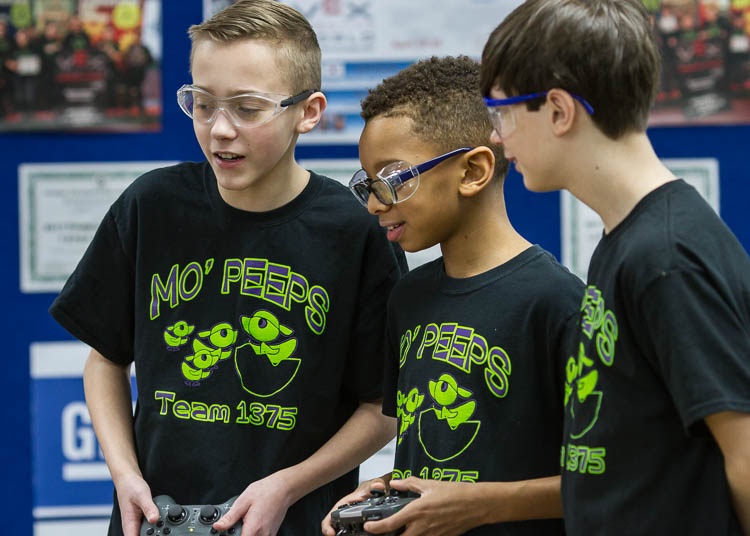 Caleb Rose, 13, (left); Micah Shamly, 12; and Jack Roy, 12, (right), all students at Carman-Ainsworth Middle School, demonstrate driving the robot and picking up objects. The students are members of the Carman-Ainsworth Middle School team traveling t