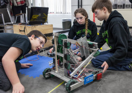 Parker Oosterhof, 12, (left); Lydia Minzey, 12; and Alex Wickham, 13, (right) work to program a robot for competition. The students are members of the Carman-Ainsworth Middle School robotics team traveling to Louisville, Kentucky for the world roboti