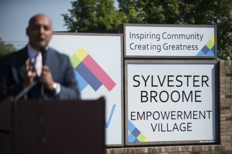Dr. Jawad Shah, center, gives a speech during the ribbon cutting at the Sylvester Broome Empowerment Village Friday, June 29, 2018 in Flint.