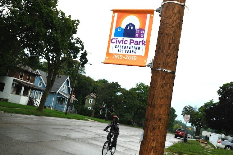 A child bicycles past one of the orange signs on Dayton Avenue celebrating Civic Park's centennial.