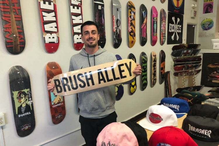 Jennings Harper, owner of Brush Alley Skateshop, shows off the new custom boards available at his shop, located at 111 E. Third St. in downtown Flint.