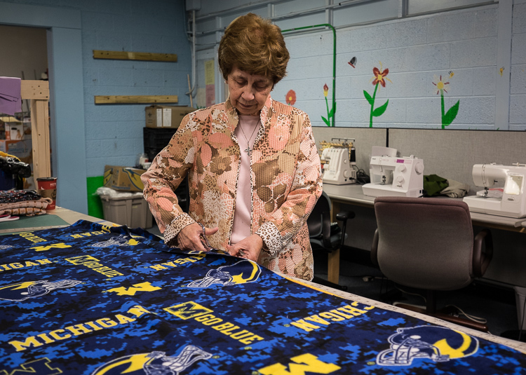 Sister Carol Weber works on a stadium blanket in the sewing center at St. Luke N.E.W. Life Center. She works hands-on as well as her administrative duties.