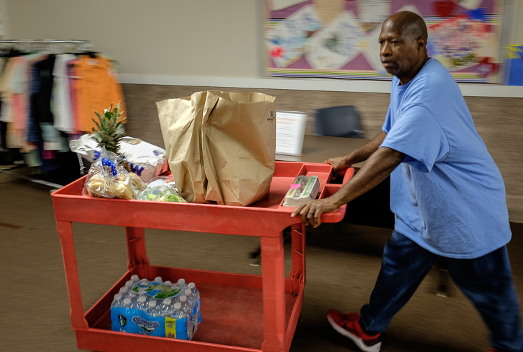 Employee Terry Taylor wheels a food donation toward a patron's car at St. Luke N.E.W. Life Center. St. Luke's receives food donations but gets food from the Food Bank of Eastern Michigan.