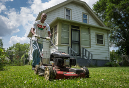 Quintin Evans uses a mower borrowed from the Community Tool Shed to mow elderly neighbors' lawns.