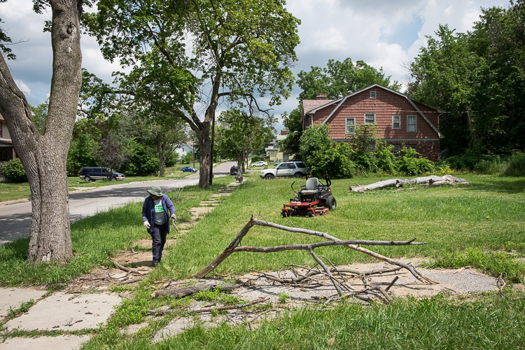 Jean Harrison of Flint looks for debris that could damage the tool shed's zero degree turn mower.
