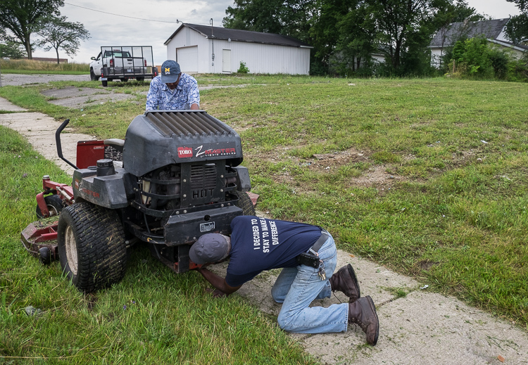 Hurb Pitts puts a belt back on a mower for Deacon Darris Berry at Shiloh Missionary Baptist Church.