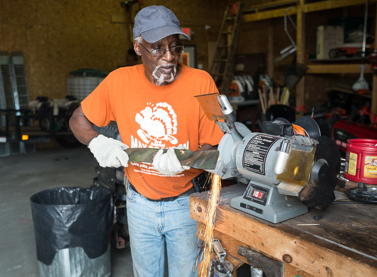 Hurb Pitts sharpens a lawn mower blade at the Community Tool Shed, located on King Avenue in Flint.