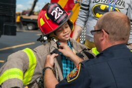 A child tries on firefighter equipment during a previous UM-Flint Touch-a-Truck.