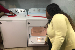 Chia Morgan, treasurer for Well of Hope, shows off the new dryer donated to Durant-Tuuri-Mott.